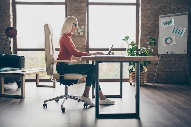 멋진 자신감 작업자 앉아 테이블의 전체 크기 프로필 측면 사진 컴퓨터 유형 문서 작업 프로젝트는 회사 사무실 로프트에서 오렌지 터틀넥 녹색 바지 바지를 착용합니다.