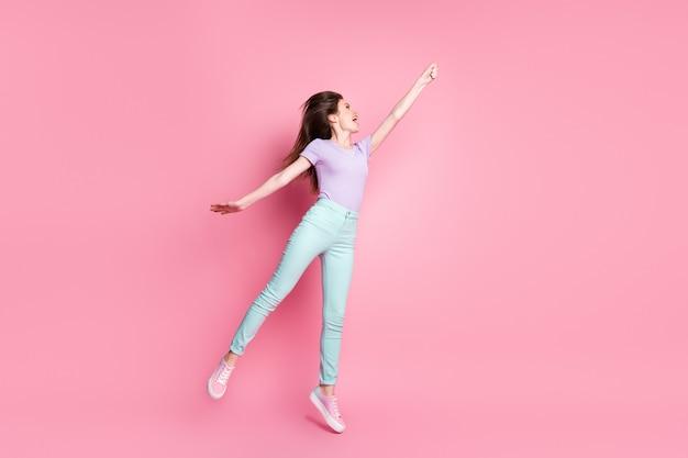 Полноразмерное фото сбоку сумасшедшей жизнерадостной девушки в прыжке, удерживая руку, ловят зонтик, ветер, ветер, летать, носить фиолетовые кроссовки, изолированные на розовом цветном фоне