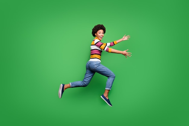 펑키 미친 아프리카 미국 소녀 점프 달리기의 전체 크기 프로필 측면 사진은 빠른 포옹을 원하는 그녀의 최고의 동료 착용 밝은 광택 의류