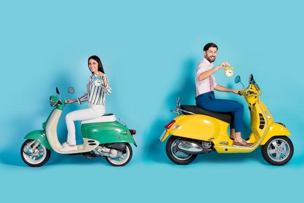 ポジティブで陽気な妻の夫のバイカーに乗るバイクホールドタイマーのフルサイズのプロフィールサイド写真目的地に時間通りに時計を運転するシャツパンツズボン孤立した青い色の壁
