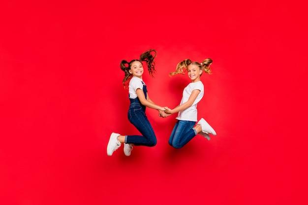Полноразмерная фотография профиля двух маленьких людей, милые дети, девочки, рождественские каникулы, прыжки, держаться за руки, чувствовать себя мечтательной одеждой, повседневная белая футболка, изолированная на красном фоне