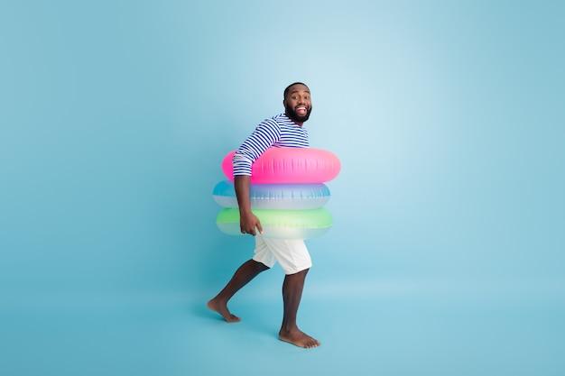フルサイズのプロフィールサイド写真ポジティブアフロアメリカンガイツーリストは休日に裸足で泳ぐ海を保持するカラフルな命の恩人はストライプのベストホワイトショーツを着用する孤立した青い色の壁