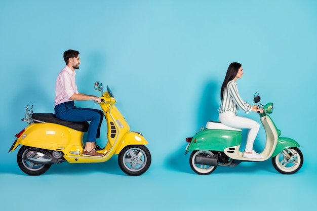 Full size profile side photo of positive cheerful man girl drive yellow green chopper enjoy freedom journey wear white striped shirt pants trousers pink isolated over blue color wall