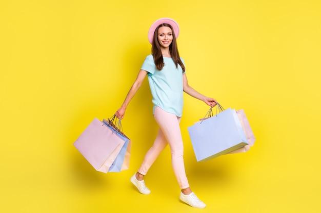 Полноразмерный профиль, фото сбоку, позитивная туристическая девушка, идите гулять по copyspace, покупайте покупки вне распродажи, покупайте, держите сумки, носите голубую розовую футболку, брюки, брюки, изолированные, яркий блеск, цветной фон