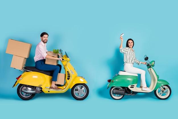 Полноразмерный профиль, фото сбоку, два человека, водитель-всадник, водят желто-зеленый мотоцикл, покупка покупок, транспортные коробки, оплата кредитной картой, одежда, торжественная одежда, изолированная, синяя стена.