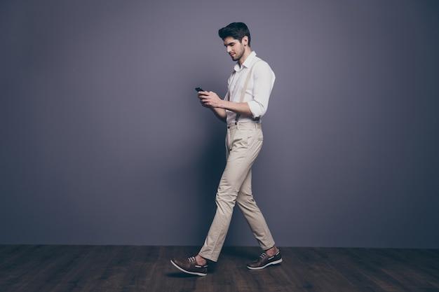 Полноразмерный боковой портрет сконцентрированного парня, идущего по сторонам, копирует пространство, использует смартфон в чате со своими коллегами по работе, одетыми в красивую одежду.