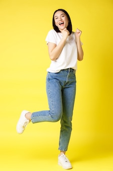 Full size shot of happy asian woman dancing and jumping from happiness, winning and celebrating victory, posing over yellow.