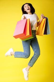 쇼핑 가방과 함께 점프 하 고 행복 하 게 웃 고, 노란색 아름 다운 아시아 여자의 전체 크기 샷.