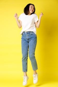 평온한 아시아 여자 점프와 춤, 재미, 청바지와 노란색 위에 흰색 티셔츠에 포즈의 전체 크기 샷.