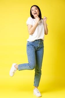 Полноразмерный снимок счастливой азиатской женщины, танцующей и прыгающей от счастья, побеждающей и празднующей победу, позирующей на желтом фоне.