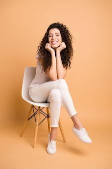 편안한 의자에 앉아있는 놀라운 아가씨의 전체 크기 세로 사진은 작업 일을 시작하도록 영감을 받았습니다.