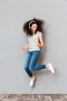 Full size view of playful female dancing and partying with waving hair against grey wall while listening music in earphones