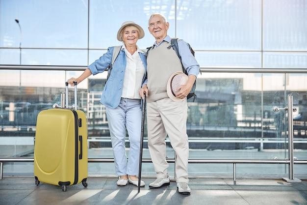 쾌활한 아가씨와 건물 근처에 서있는 그녀의 수석 회색 머리 남편의 전체 크기 초상화