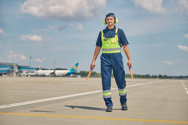 Full-sized portrait of a serious aircraft marshaller with wands walking alone across the airfield