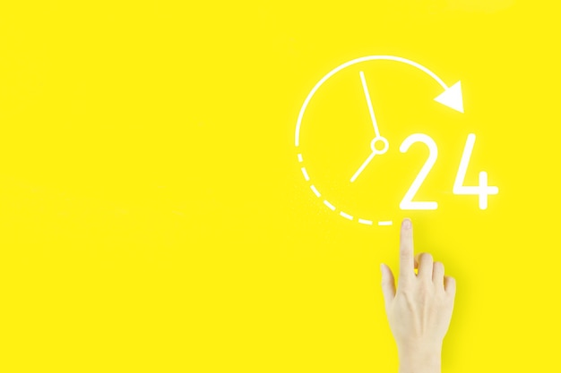 フルタイムのサービスコンセプト。黄色の背景にホログラム247終日終夜アイコンで指している若い女性の手の指。ビジネスボタン24時間サービス