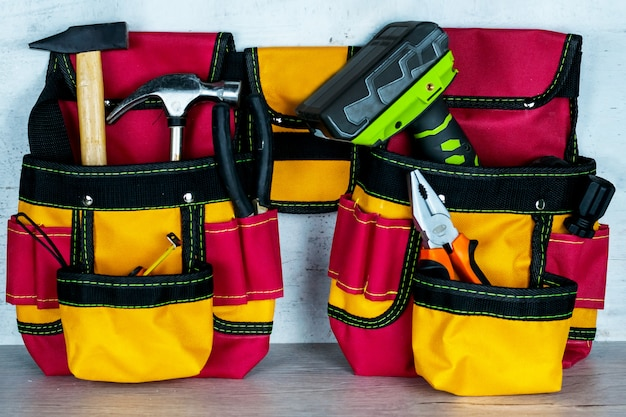 Full tool bag on a white concrete wall background.