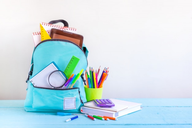 Full turquoise school backpack with stationery on table.