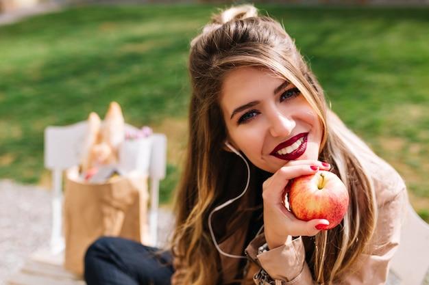 Ritratto completo della bella ragazza appoggiata al viso con la mano e guarda con interesse dopo aver acquistato il cibo.