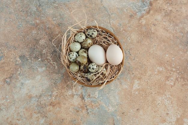 Cestino di vimini pieno con uova di quaglia sul tavolo di marmo.
