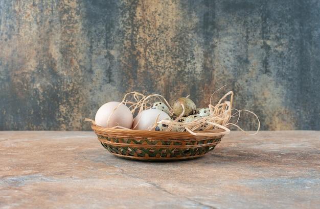 Cesto di vimini pieno con uova di quaglia su marmo
