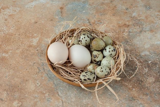 Полная плетеная корзина с перепелиными яйцами на мраморном столе.