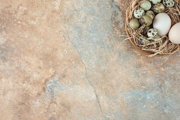 大理石のテーブルにウズラの卵が入ったフルウィッカーバスケット。