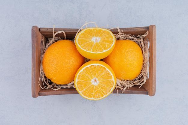 Cesto di legno pieno di arance affettate dolci. foto di alta qualità