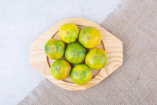 Полная деревянная тарелка кислых мандаринов на белом