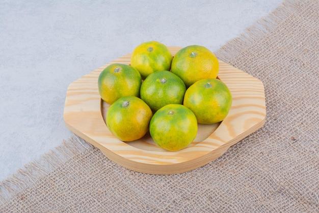 Piatto di legno pieno di mandarini acidi su sfondo bianco. foto di alta qualità