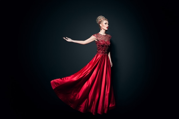 Полное изображение прекрасной молодой женщины, одетой в длинное свободное красное платье с поднятыми руками, на черном фоне. горизонтальный вид.