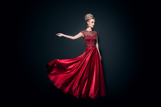 Fulll length image of a wonderful young woman dressd in a long fluing red dress with raised hand, over black background.