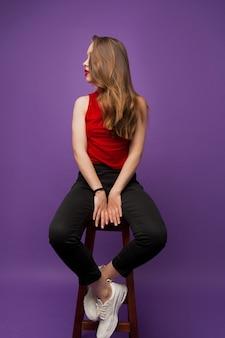 明るい上で目をそらしている長いウェーブのかかった髪の椅子に座っているエレガントな女性の完全な肖像画