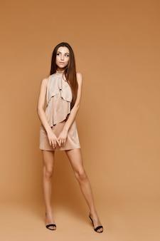 Модный снимок в полный рост молодой модели с идеальным стройным телом и длинными ногами в коротком бежевом платье на бежевой поверхности