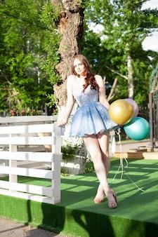 Портрет в полный рост очаровательной молодой женщины в нарядном коротком синем корсетном платье, стоящей на ...