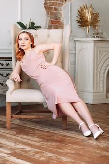 Портрет в полный рост рыжеволосой женщины в бежевом шелковом платье, сидящей в кресле против ба ...