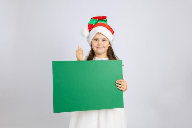 白いドレスとクリスマスのノームの帽子をかぶって踊り、ホルを楽しんでいる陽気な女の子の全身像...