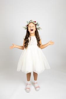 エレガントな白いドレスとクリスマスリースで分離された笑う楽しい女性の全身像...