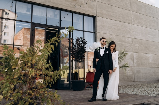 Fulllength portrait of stylish newly married european couple