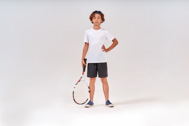 テニスラケットを保持し、隔離されたカメラを見ている自信を持って10代の少年のフルレングスのショット