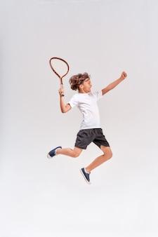 灰色の背景スタジオ上に分離されたテニスラケットでジャンプする10代の少年のフルレングスのショット