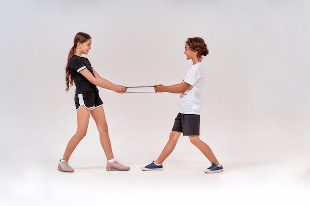 저항 밴드와 함께 운동하는 동안 즐거운 십대 소년과 소녀의 전체 길이 샷