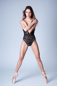 Fulllength studio portrait of a beautiful girl with a sports figure in a lace bodysuit on pointe