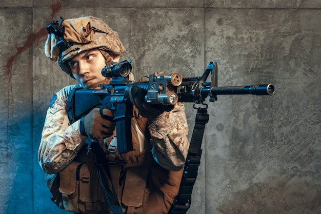 Fully equipped army soldier in camo uniform and helmet, armed with pistol and assault service rifle