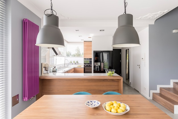 オーブン、大型の黒い冷蔵庫、長い紫色のラジエーターを備えた設備の整ったモダンなキッチンインテリア