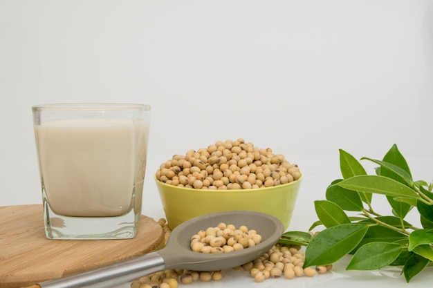 Fully soy beans in the bowl and spoon on white table .