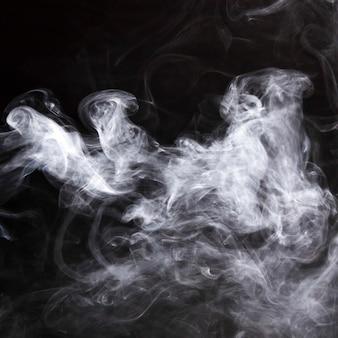 연기의 연기가 검은 배경 위에 퍼졌습니다.