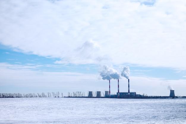 雲と白い雪のある青い空の表面にある工場の発煙煙突