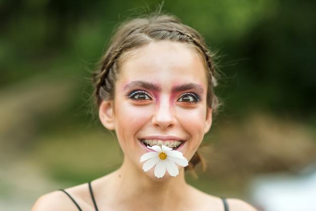 입에 데이지 꽃과 가짜 행복 한 젊은 여자. 뷰티 스프링. 봄. 젊음, 개화 꽃.