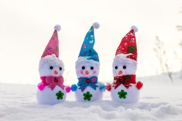 Веселая и дружная компания трех игрушечных снеговиков на снегу_