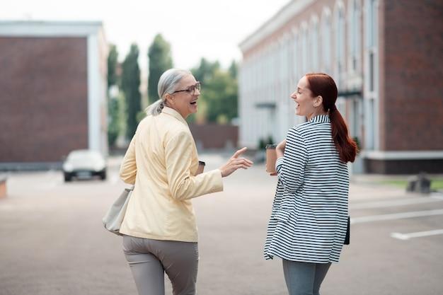 楽しさと幸福。お互いを見ながら屋外で笑っているスタイリッシュな服を着た2人のビジネス女性の背面図